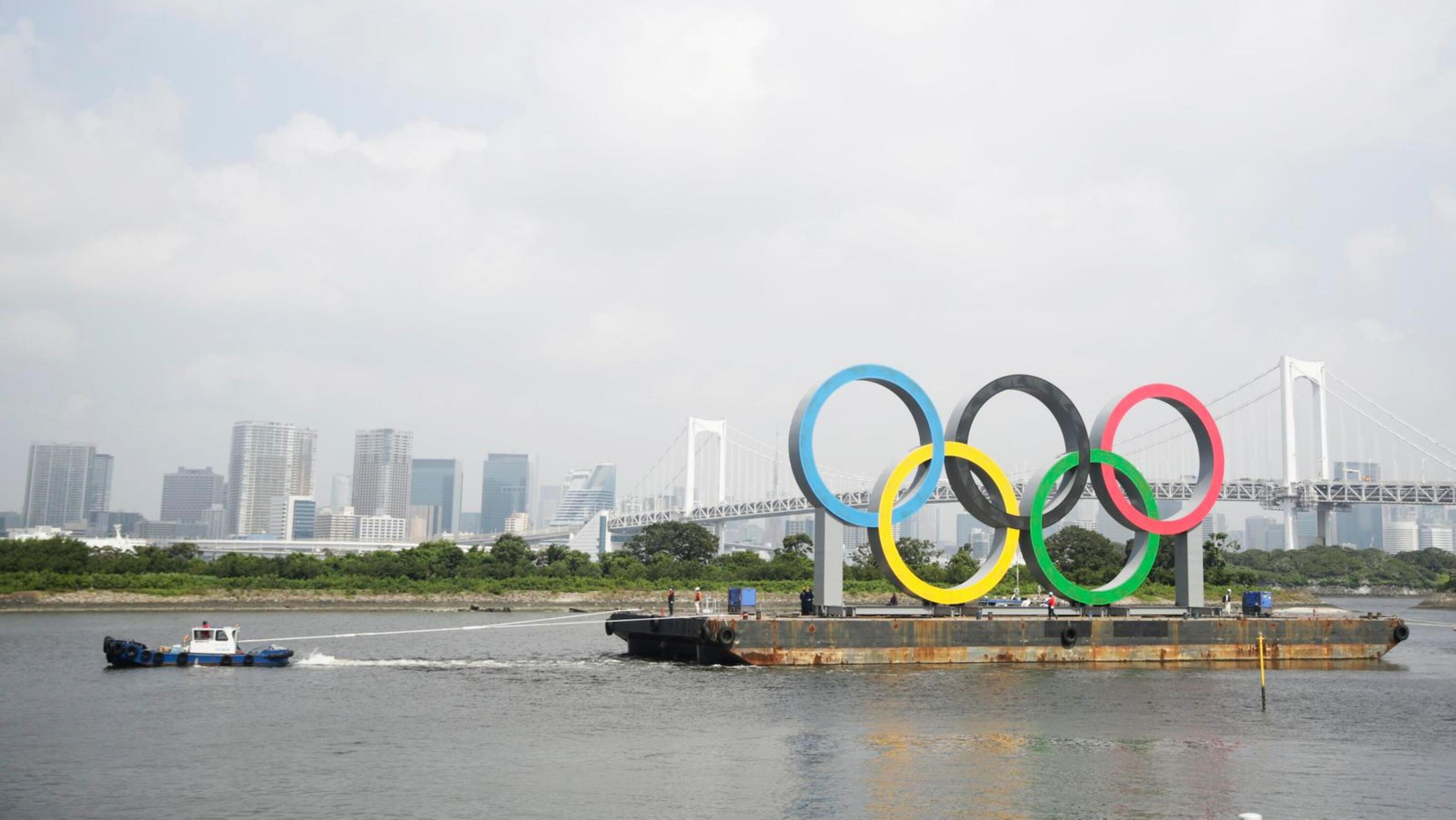 Tugboats move a symbol installed for the Olympic and Paralympic Games Tokyo 2020 on a barge gets moved away from its usual spot off the Odaiba Marine Park for a safety inspection and maintenance, in Tokyo