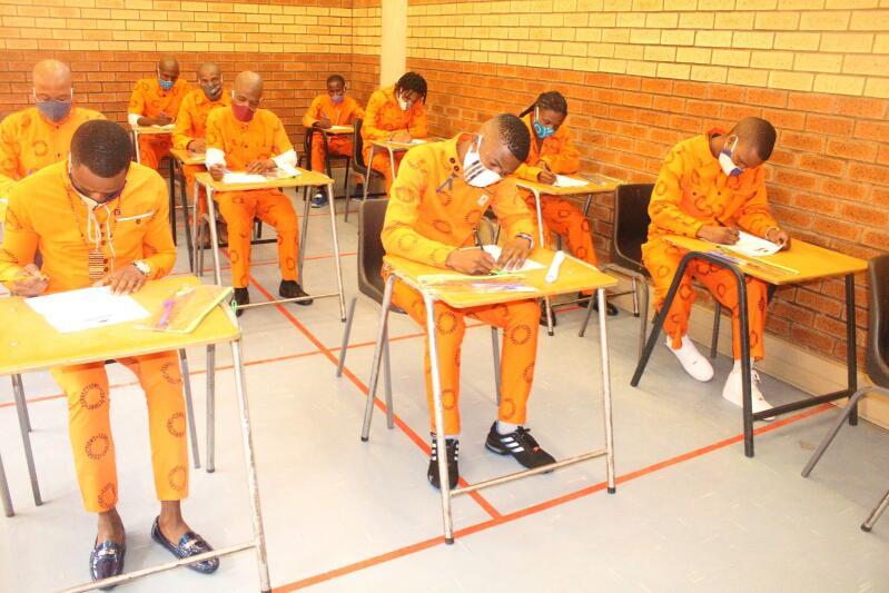 Inmates writing exams.