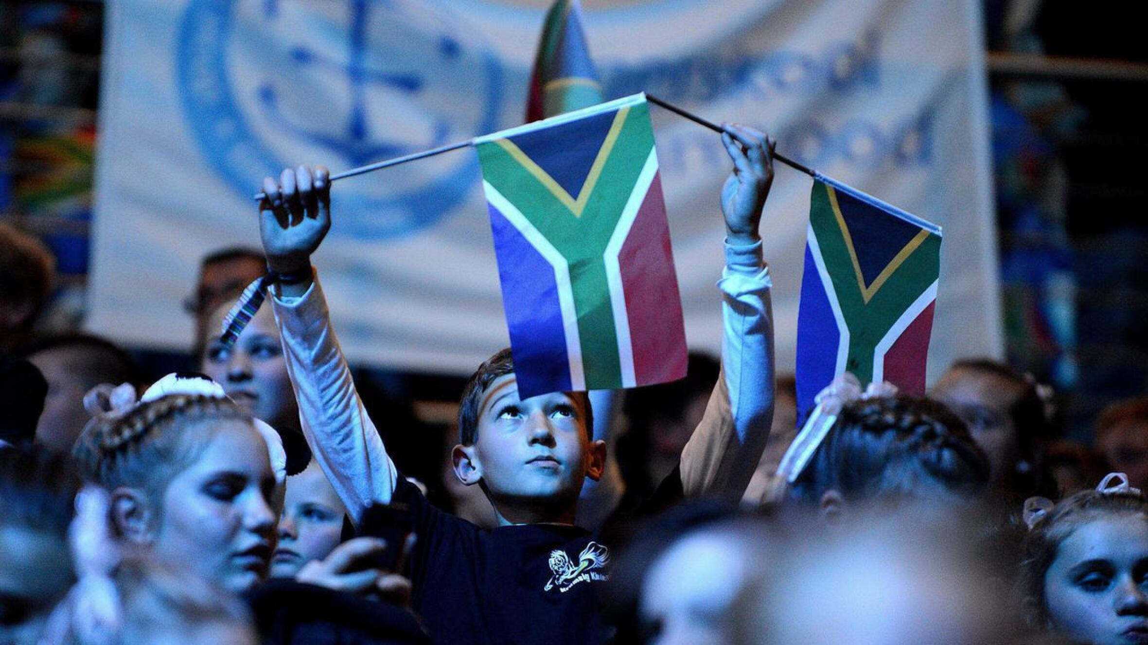 A young boy raising the South African flag