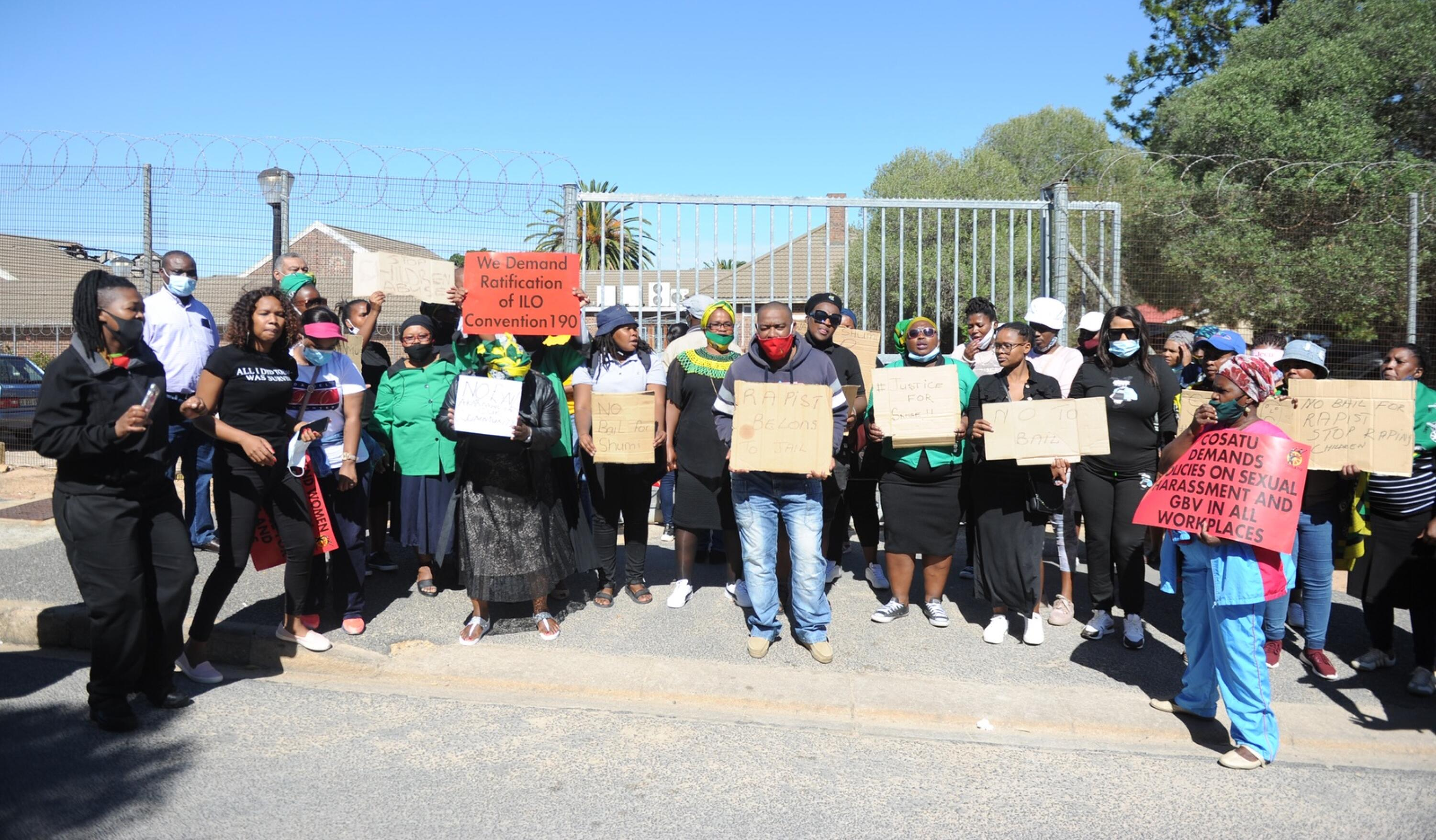 Protesters hold up placards outside a courthouse.