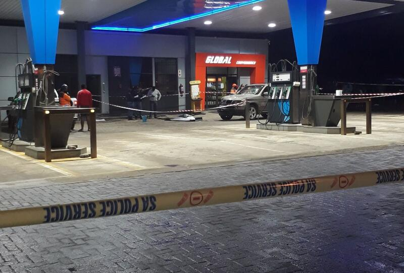 A car at a petrol station with police tape.