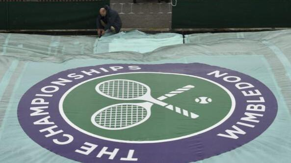 A member of the ground staff checks covers on an outdoor court during rainfall at Wimbledon in 2015