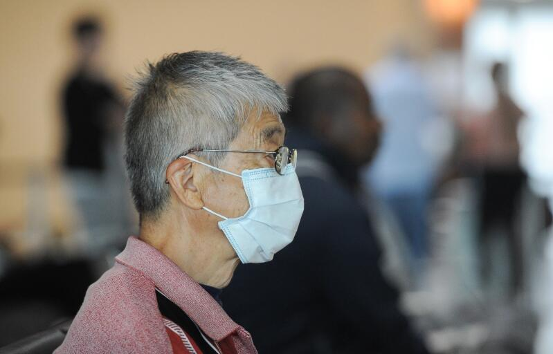 A Chinese man in a pink shirt wears a face mask.