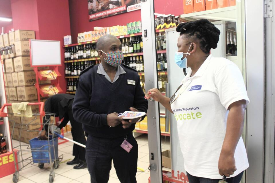 MEC Nomafrench Mbombo speaking to the security at the local alcohol retailer about the dangers of alcohol for pregnant women.