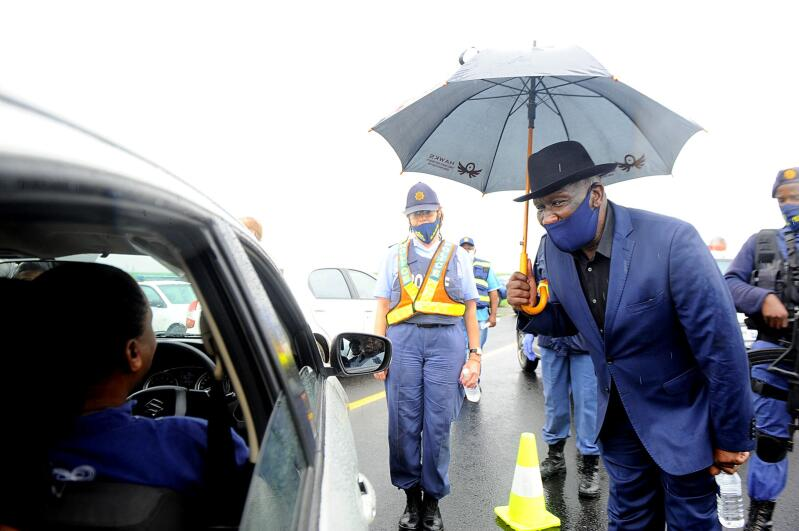 A man in a blue jacket and a black hat and wearing a face mask crouching under an umbrella while talking to a motorist.