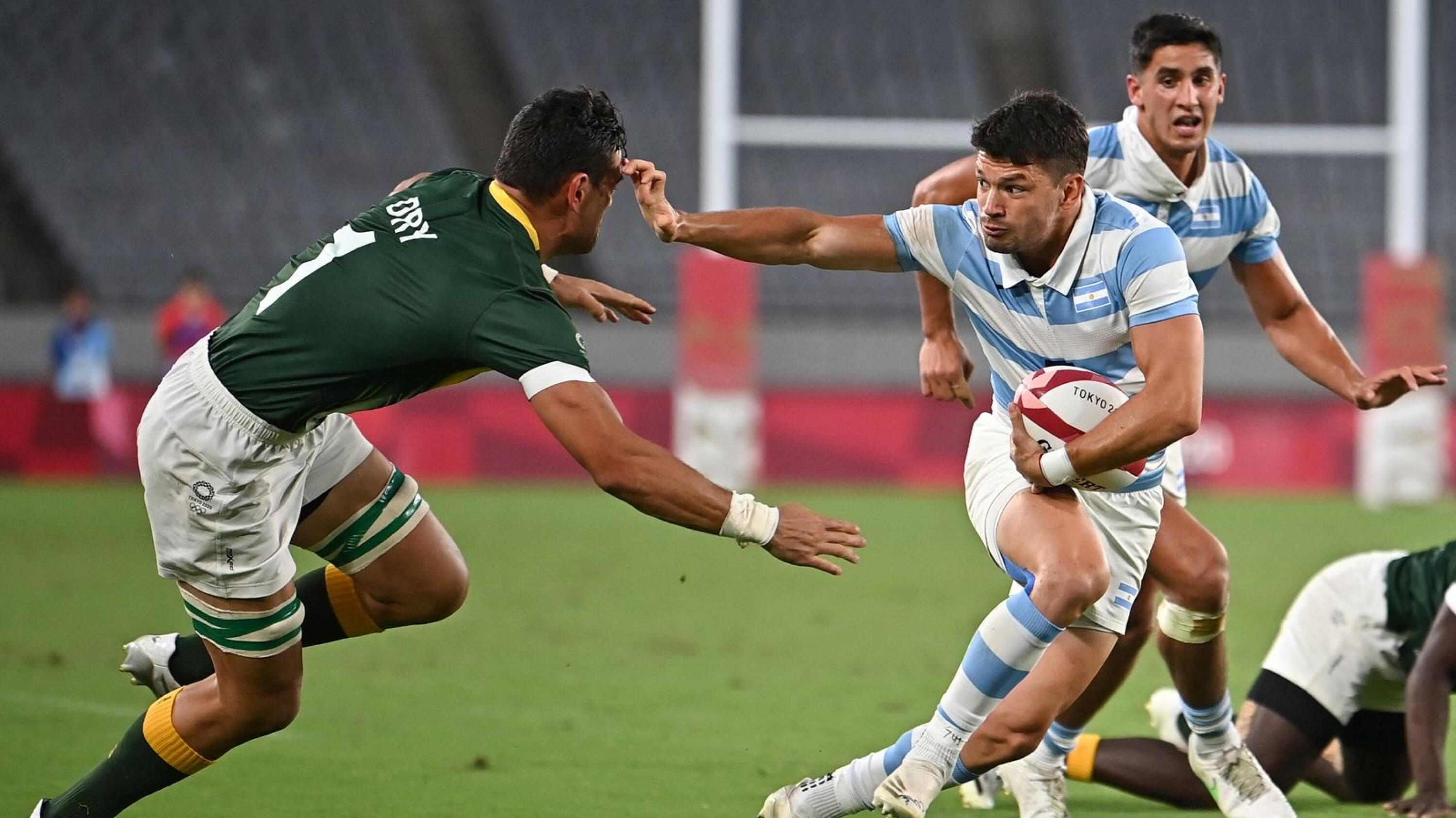 Argentina's Lautaro Bazan Velez (front R) evades a tackle by South Africa's Chris Dry in the men's Tokyo Olympics quarter-final rugby sevens match at the Tokyo Stadium in Tokyo on Tuesday