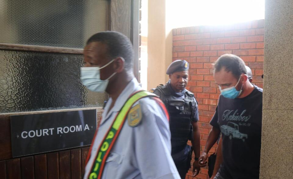 Stefanus Johannes Fourie enters the courtroom flanked by police officers.