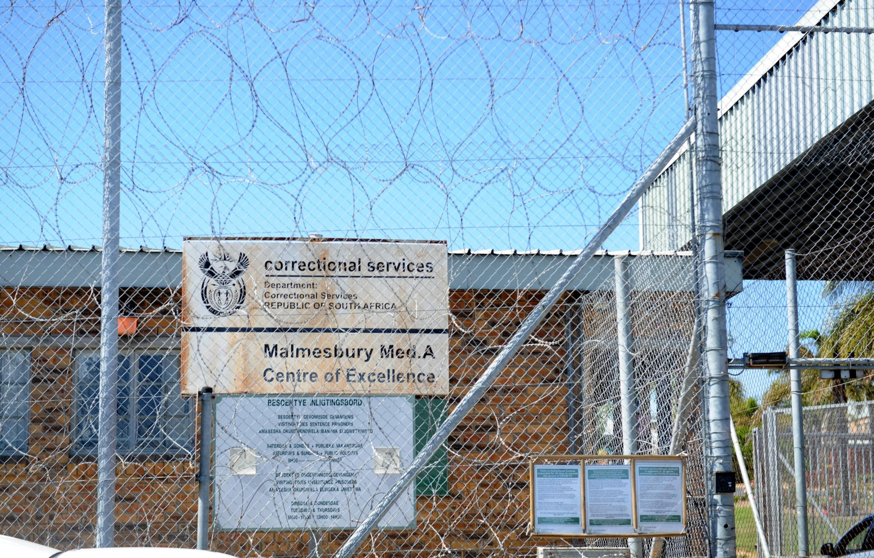 Exterior view of a brick correctional services building behind a barbed-wire fence.