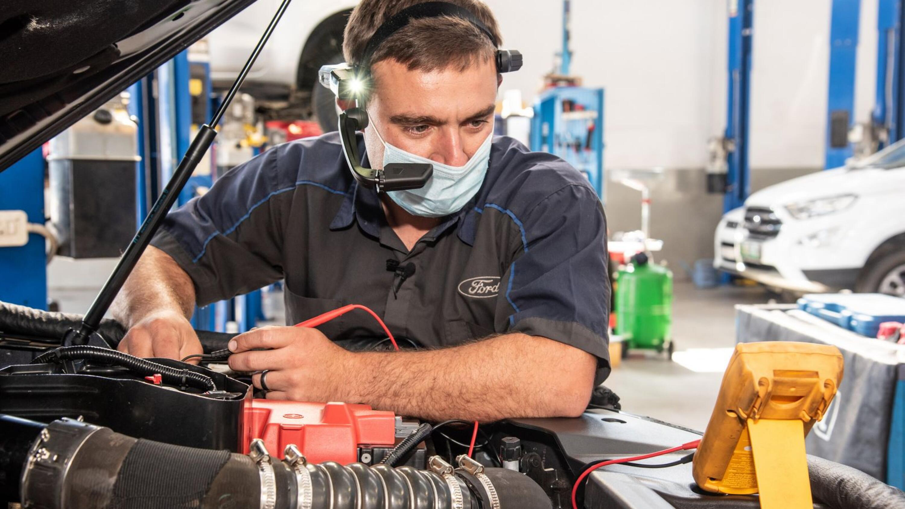 A Ford technician works on a customer's vehicle using an augmented reality headset.